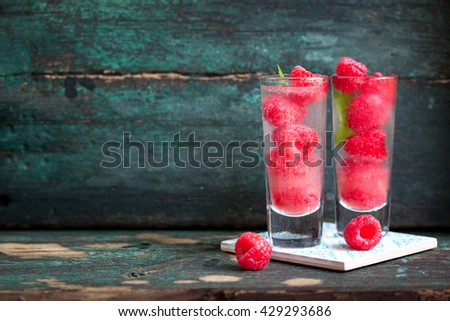 Homemade summer cold raspberry cocktail with ice, berry syrup and alcohol in glasses on a vintage background, horizontal with place for text - stock photo
