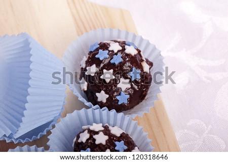 homemade sweet chocolate pralines with blue and white stars - stock photo