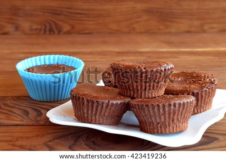 Homemade sweet pastry. Home tasty brown cupcakes on a wooden table. Sweet muffins are made of eggs, butter, chocolate, cocoa powder, sugar, flour. Cocoa cupcakes - stock photo