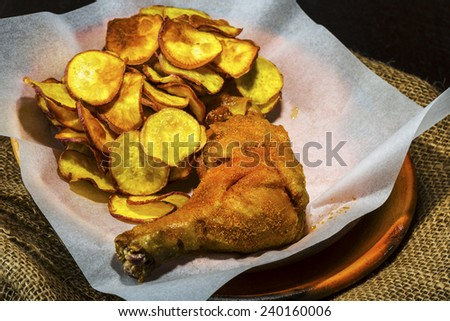 Homemade sweet potatoes chips and a chicken leg in a rustic clay plate on wood table - stock photo