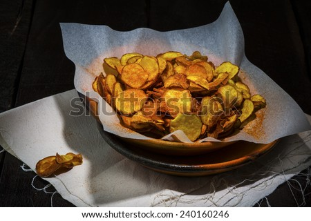 Homemade sweet potatoes chips in a rustic clay plate on wood table - stock photo