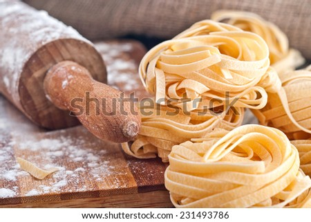 Homemade tagliatelle. Raw pasta on the wooden table. - stock photo