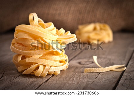Homemade tagliatelle. Uncooked pasta on the wooden table.  - stock photo