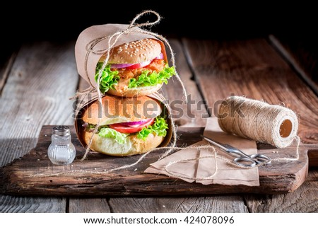 Homemade takeaway burger wrapped in paper - stock photo
