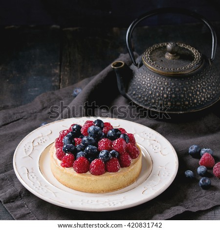 Homemade tart with custard, fresh raspberries and blueberries, served on white vintage plate with iron teapot on textile napkin over old wooden table. Dark rustic style. Square image - stock photo