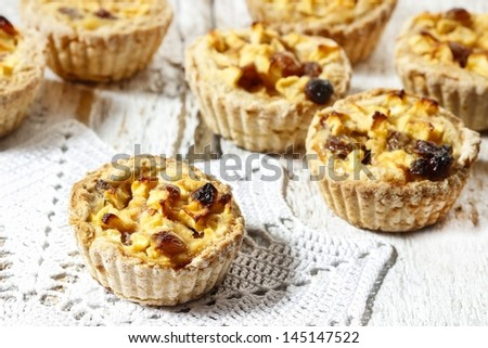 Homemade tart with dried fruits and fresh apples on white wooden background, selective focus