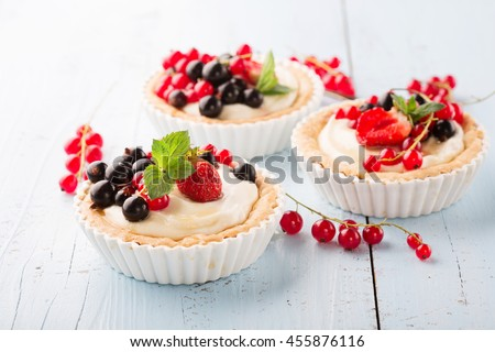 Homemade Tartlets with cream and fresh berries - ripe red and black currants, strawberries on blue rustic wooden table, selective focus - stock photo