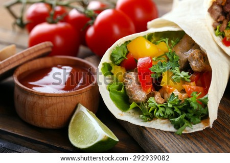 Homemade tasty burrito with vegetables on cutting board, on wooden background