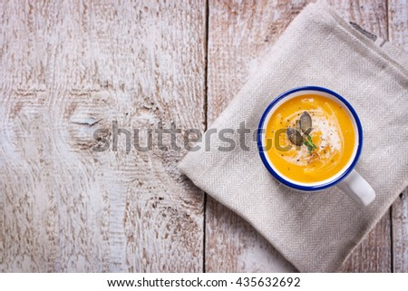 Homemade tasty creamy pumpkin soup puree in a bowl on a wooden background, top view, copy space - stock photo
