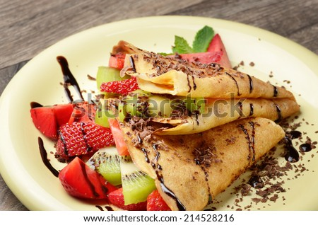 Homemade tasty crepes with strawberries, kiwi and chocolate syrup - stock photo