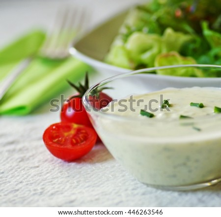 Homemade tasty organic fresh vegetables salad in white plate with sour yogurt dressing in a glass bowl on white served table and fork on green napkin. Salad with dressing. Healthy food concept. - stock photo