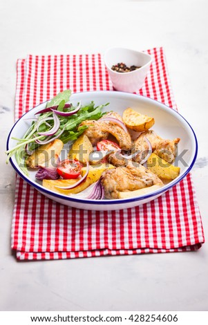 Homemade tasty roasted chicken wings with roasted potato with vegetables in an enamel bowl, closeup - stock photo