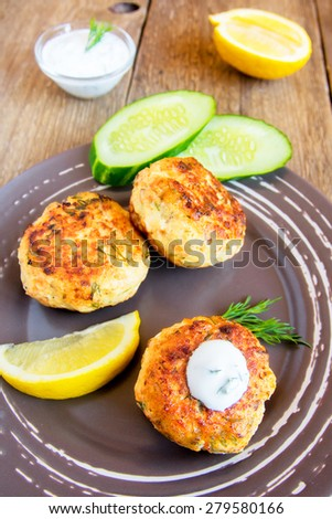 Homemade thai fish cakes (cutlets) with white sauce, dill and lemon on plate and rustic wooden table - stock photo
