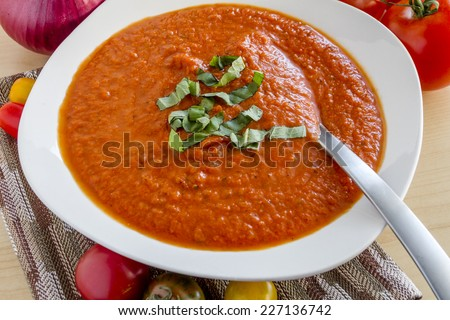 Homemade tomato and basil soup in white round bowl sitting on brown striped napkin surrounded with fresh vegetables - stock photo
