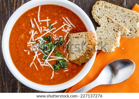 Homemade tomato and basil soup sprinkled with parmesan cheese in white bowl with spoon and whole grain bread - stock photo
