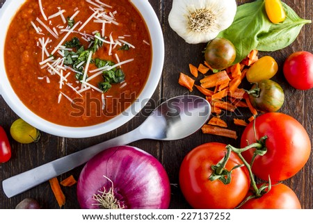 Homemade tomato and basil soup sprinkled with parmesan cheese in white bowl with spoon surrounded by fresh vegetable ingredients - stock photo
