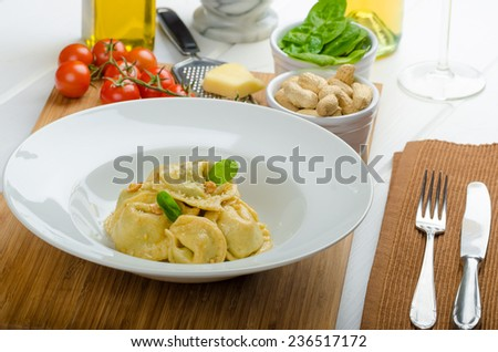 Homemade tortellini stuffed with spinach and garlic, topped with lightly buttered reduction with nuts