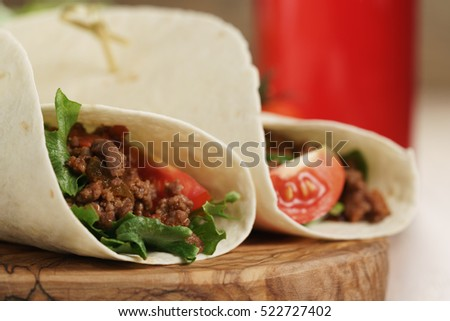 homemade tortilla with beef, frillice and vegetables and drink on wooden board, shallow focus