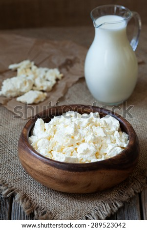 Homemade traditional cottage cheese ogranic dairy product with milk in rustic wooden dish on vintage kitchen table background Dark food photo, rustic style and natural light - stock photo