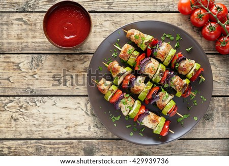 Homemade turkey or chicken meat shish kebab skewers with ketchup sauce, and tomatoes on rustic wooden table background. Traditional barbecue grill shish food - stock photo