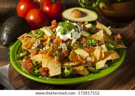 Homemade Unhealthy Nachos with Cheese, Sour Cream, and Vegetables - stock photo