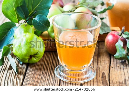 Homemade vegan apple juice and fresh apples and quince on rustic wooden table - stock photo
