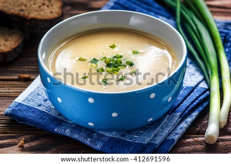 Homemade vichyssoise cream soup served with chives, in blue bowl on wooden table. - stock photo