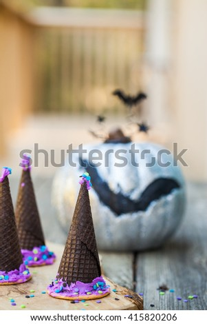Homemade waffle cones cookies in the form of a Halloween witch hat decorated with purple icing on a wooden background. Selective focus on the hat. Also available in horizontal format.   - stock photo
