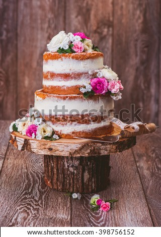 Homemade wedding naked cake  decorated with flowers on wooden cut stand - stock photo