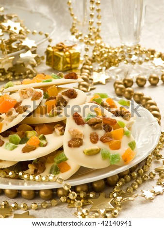 Homemade white chocolate cookies decorated with dried apricots, pistachios, raisin, candied fruits and walnuts. Shallow dof. - stock photo