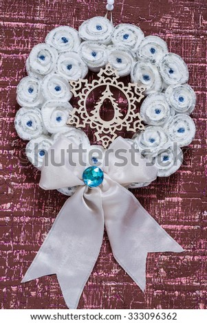 Homemade white Christmas wreath with snowflakes on burgundy wooden background - stock photo