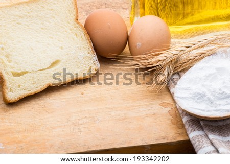 Homemade whole bread and flour on wooden background - stock photo