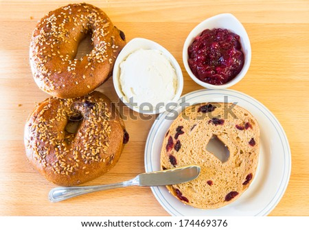Homemade whole grain bagels with sesame seeds and cranberries served with cream cheese and lingonberry jam. - stock photo