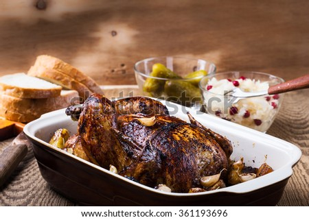 Homemade whole roasted chicken with  garlic and potatoes in ceramic pan served with pickles and sauerkraut - stock photo