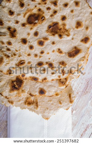 Homemade whole wheat flour tortillas on a wooden table. Unleavened bread. - stock photo