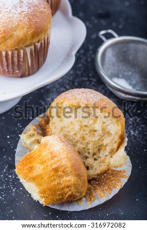 Homemade yeast buns on white plate on black table - stock photo