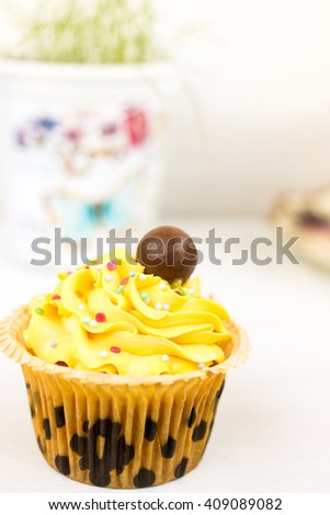 Homemade yellow cupcake decorated with sweet icing and chocolate berry. - stock photo