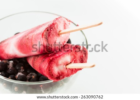 Homemade yogurt ice pops with fresh black berry  for hot summer days on a white table - stock photo