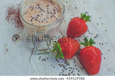 Homemade yogurt in a jar with strawberry, seeds and cacao. Dessert with strawberries on a white wooden background. Fresh strawberry with yogurt. Selective focus. Shallow depth of field. Horizontal. - stock photo