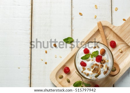 Homemade yogurt or sour cream in a glass on the white wooden table