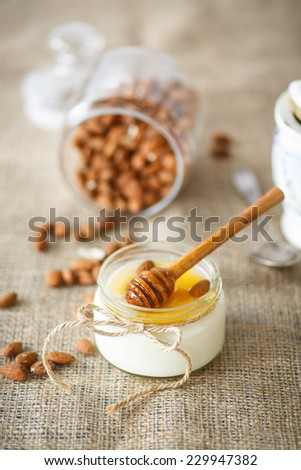 homemade yogurt with honey and nuts in a glass jar - stock photo