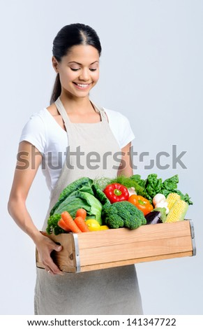 Homemaker chef holding a wooden crate full of fresh raw organic produce vegetables - stock photo