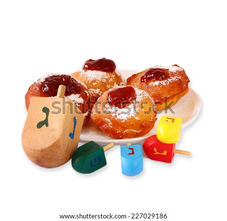 homemdae doughnuts for Hanukkah (Jewish festival) and wooden dreidel (spinning top) isolated on white - stock photo