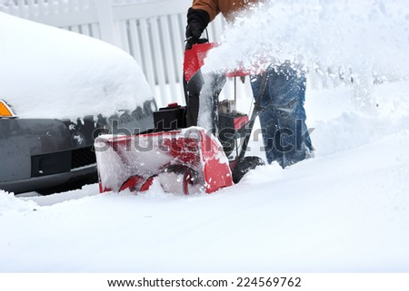 homeowner clearing snow from driveway with snow blower - stock photo