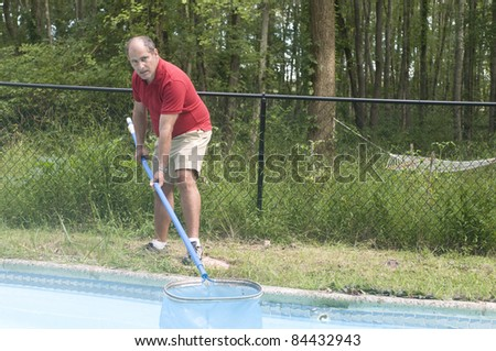 homeowner swimming pool maintenance man cleaning swimming pool skimming debris from water horizontal composition