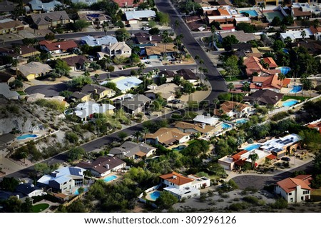 Homes houses from high overhead aerial neighborhood development swimming pools and streets - stock photo
