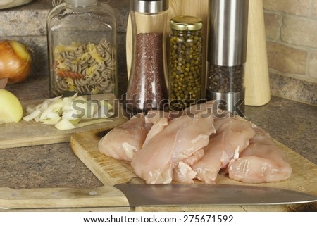 Homework chicken meat, slicing chicken breast fillet, kitchen table with ingredients for cooking - stock photo