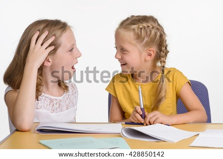 Homework process went wrong. The elder sister tries to help while young girl laughs in response. Stationery on the wooden desk. - stock photo
