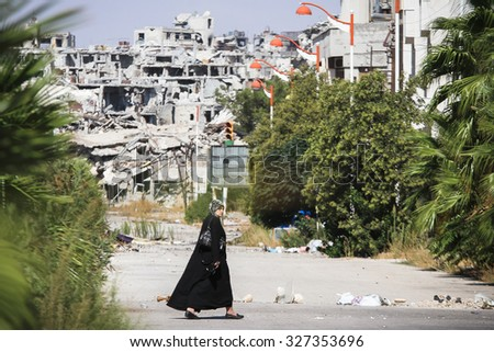 Homs, Syria, September 2013 A woman walks near a residential area in the city of Homs destroyed in the fighting between the rebels of the Syrian National Army - stock photo