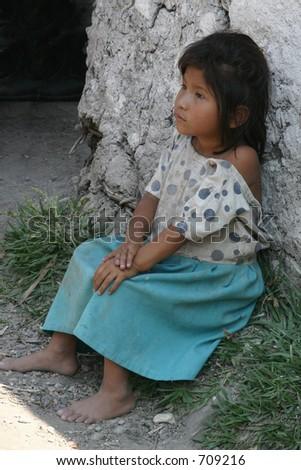 Honduran Girl Sitting by Doorway - stock photo